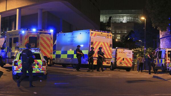 Armed police positioned near emergency vehicles after reports of an explosion at the Manchester Arena during an Ariana Grande concert in Manchester, England Monday, May 22, 2017. - Sputnik Беларусь